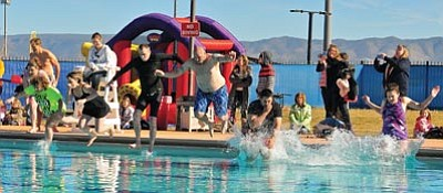 Matt Hinshaw/The Daily Courier<br>Participants in the 9th annual Polar Bear Splash leap into the Mountain Valley Splash pool Saturday in Prescott Valley. The water was 41 degrees Fahrenheit.