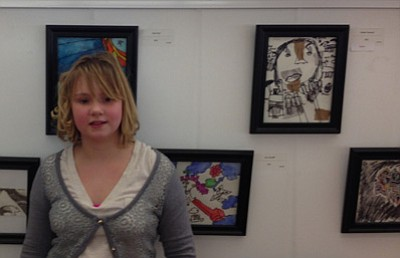 Tamara Sone/The Daily Courier<br> Budding artist Ananise Toth, 10, stands in front of a wall decorated with works of art all created by children in the 'Tis Art Center STEPS Children's Art School.