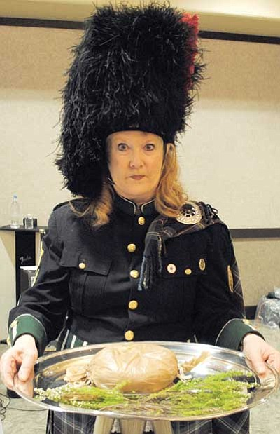 Tamara Sone/The Daily Courier<br> Piper Denise Robinson shows off a platter of Haggis – a traditional Scottish dish comprised of sheep heart, liver and lungs; minced with onion, oatmeal, suet, spices, salt and stock, and traditionally encased in the animal's stomach and simmered for approximately three hours.