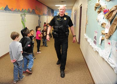 Les Stukenberg/The Daily Courier<br> Prescott Valley police officer Jason Lohman does a school check at Lake Valley Elementary School Monday afternoon. The Prescott Valley Police Department aims to do daily random checks at all the schools in their jurisdiction.