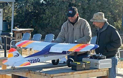 Matt Hinshaw/The Daily Courier<br>Casa de Aero R/C Club members Jack Hardy, left, and Walter Wilken prepare Hardy's new Eflite Carbon Z Cub for its maiden flight on Oct. 31, 2013, at the Casa de Aero Airfield on the campus of Embry-Riddle Aeronautical University in Prescott.