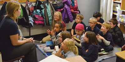 Aaron Rosberg/Courtesy photo<br> First-graders listen to teacher Emily McKeown at Trinity Christian School. Tuition costs for students in local private schools average just over $5,000 a year.