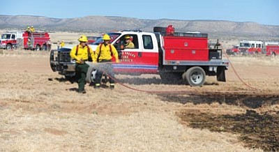 Les Stukenberg/The Daily Courier<br>Chino Valley firefighters spray down the edge of a 100-acre grass fire near Big Springs Ranch Road and Runway Road in Paulden Wednesday afternoon.