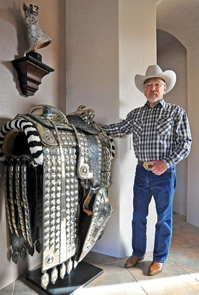 "Matt Hinshaw/The Daily Courier<br>Leatherworker Dusty Johnson poses next to a vintage silver horse saddle he restored. ""If I don't do these, they will be gone"" for future generations, Johnson said."