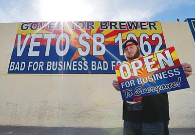 "Matt York/The Associated Press<br>Josh Deinert holds up an anti-Senate Bill 1062 sign that reads ""Open For Business To Everyone"" Wednesday."