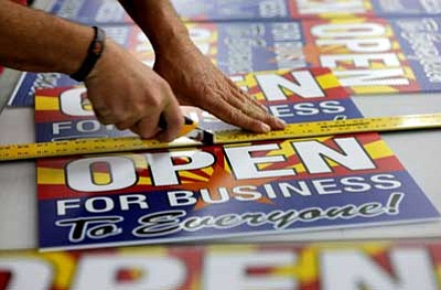 """Matt York/The Associated Press<br>Tom Cushing, a production expert at Fast Signs, cuts down a sheet of anti-Senate Bill 1062 signs that read """"Open For Business To Everyone"""" Wednesday in Phoenix."""
