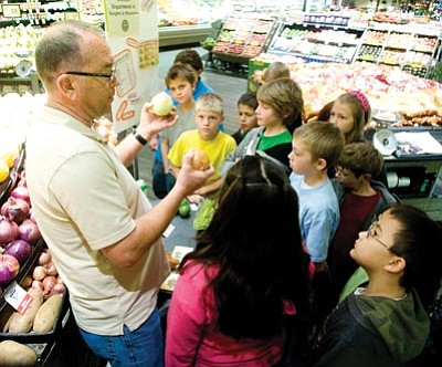 Les Stukenberg/The Daily Courier<br>Mike Wright explains how produce is priced as Mountain View Elementary School fourth-graders learn about weights and measures during a hands-on presentation by the Arizona Department of Weights and Measures at the Prescott Valley Safeway store Wednesday morning.