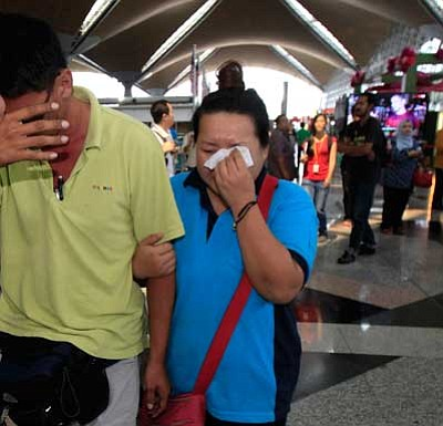 Lai Seng Sin/The Associated Press<br> A woman wipes her tears after walking out of the reception center and holding area for family and friend of passengers aboard a missing Malaysia Airlines plane, at Kuala Lumpur International Airport in Sepang, outside Kuala Lumpur, Malaysia, Saturday.