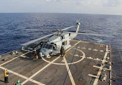Navy Media Content Service, Senior Chief Petty Officer Chris D. Boardman/The AP<br> A U.S. Navy helicopter lands aboard Destroyer USS Pinckney during a crew swap before returning to a search and rescue mission for the missing Malaysian airlines flight MH370 in the Gulf of Thailand on Sunday.
