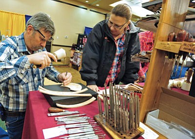 Matt Hinshaw/The Daily Courier<br> Barb Hagins watches her husband Scott try out a leather stamp at a vendor booth.