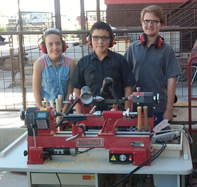 Courtesy photos<br> Students, from left, Shannon Page, Juan Favela and Grant Malinowski with the school's new lathe at the Franklin Phonetic School in Prescott Valley. Below, Franklin Phonetic School shop teacher Tom Bockman works with student Timmy Young.