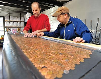 Matt Hinshaw/Courier<br> Black Hole Beer Company owners Eric Marichal, left, and Chris Mewhinney line up pennies for their bar top. They plan to open their brewery on April 19.