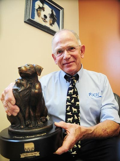 Les Stukenberg/The Daily Courier<br> Dr. Steve Dow holds the 2014 American Animal Hospital Association Practice of the Year Award that was recently presented to Prescott Animal Hospital.