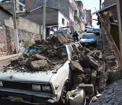 Alejandrino Gonzalez/The Associated Press<br> A parked car suffered damage when a adobe wall collapsed on it after a strong earthquake shook Chilpancingo, Mexico, on Friday.