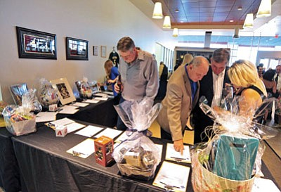Matt Hinshaw/The Daily Courier<br> Dave McCormack, front left, and others browse through items in the silent auction Saturday night during the third annual Dinner for the Diamond fundraiser event at the Tim's Toyota showroom.