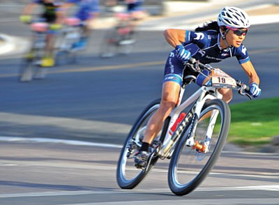 Photos by Matt Hinshaw/The Daily Courier<br>Evelyn Dong of Salt Lake City speeds around a turn during the ladies' Fat Tire Pro Criterium Friday afternoon in downtown Prescott as the 11th annual Whiskey Off-Road opened.