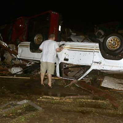 Danny Johnston/The AP<br> John Ward, an automobile and RV dealer, looks an tornado damage to one of his trucks in Mayflower, Ark., Sunday.