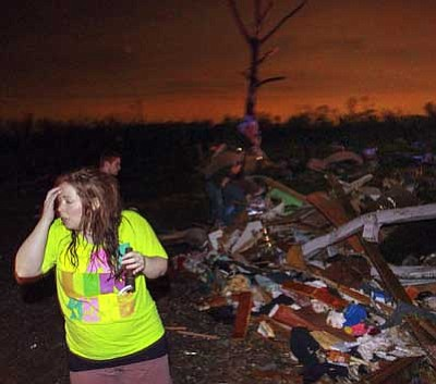 The Arkansas Democrat-Gazette, Benjamin Krain/The AP<br> Lauren Watts searches for her dog in Mayflower, Ark., Sunday after a tornado struck the town.