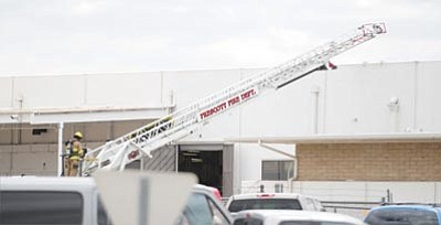 Les Stukenberg/The Daily Courier<br> A Prescott firefighter lowers the ladder from the roof of the Sturm, Ruger and Company building at the Prescott Airport Wednesday morning.