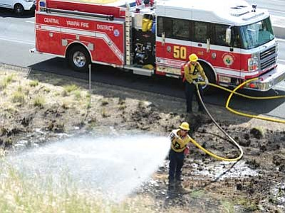 Les Stukenberg/The Daily Courier<br> Central Yavapai Fire personnel put out hot spots at one of four wildland fires that flared up along Highway 69 between Prescott and Prescott Valley Thursday morning.