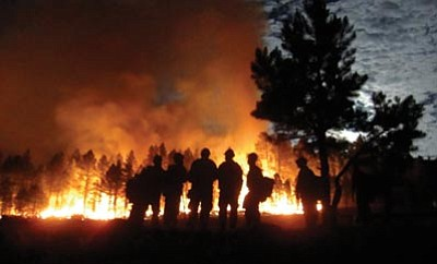 Courtesy photo<br> The Granite Mountain Hotshots assess the Las Conchas wildfire in New Mexico in 2011. The elite crew had the expertise to conduct initial attacks on fires in rough terrain in the dark.
