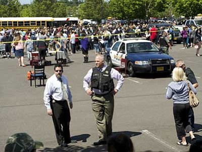 Troy Wayrynen/The Associated Press<br> Police direct parents to waiting students arriving by bus at a shopping center parking lot in Wood Village, Ore., after a shooting at Reynolds High School on Tuesday morning. A gunman killed a student at the high school east of Portland and the shooter also is dead, police said.