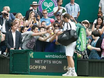 Pavel Golovkin/The Associated Press<br> Andy Murray of Britain signs autographs after his first-round match against David Goffin of Belgium at Wimbledon on Monday.