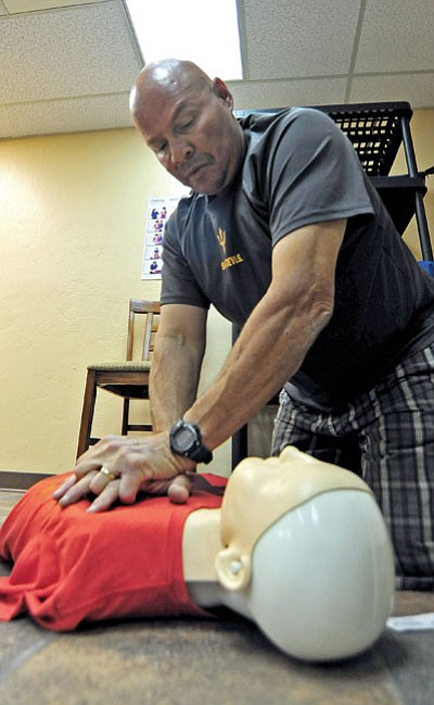 Matt Hinshaw/The Daily Courier<br>Mario Gomez practices CPR on a mannequin Wednesday morning during New Life's CPR class in Prescott.