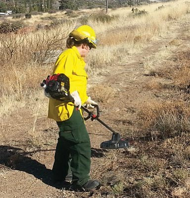Courtesy photo<br>Thanks to funding from a Arizona State Forestry Division grant, a Yarnell Fire Department crew member works on clearing a half-mile-long buffer line near the eastern boundary of Yarnell.