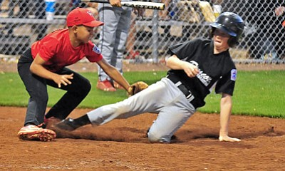 Matt Hinshaw/The Daily Courier<br>Prescott All-Star Scooter Schwartz slides across home plate while Verde Valley All-Star Dante Gabaldon tags him out Friday night during the 9-10 District 10 Little League Majors All-Star Tournament Championship at Brad Ziegler Field in Prescott.