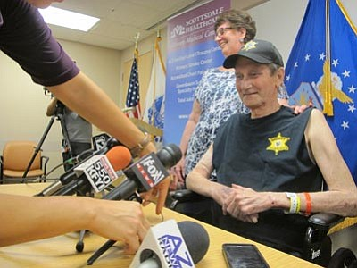 Brian Skoloff/The Associated Press<br> Maricopa County Sheriff's Office volunteer posse member Philip Grigg sits next to his wife, Elizabeth at a news conference as he prepares to leave Scottsdale Osborne Hospital. Grigg, 63, has been hospitalized for six months after being shot while trying to assist an officer who was pursuing several robbery suspects.