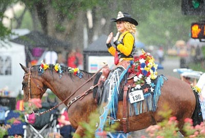 Les Stukenberg/The Daily Courier<br>Flagstaff Pro Rodeo 2014 Queen Aubrey Toler kept her smile in the rain during the Prescott Frontier Days Parade Saturday morning.