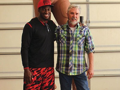 Courtesy photo<br> Washington Redskins quarterback Robert Griffin III poses with sculptor Tom White in his Prescott Valley studio.