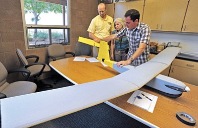 Matt Hinshaw/The Daily Courier<br> Stephen Rayleigh, owner of SWIFT Radioplanes, right, demonstrates how the Lynx UAS, Unmanned Aerial System, tail comes apart for repair or storage while John Morgan, dean of the Yavapai College Chino Valley campus and Karla Phillips, assistant dean of the YC Chino Valley campus look on Thursday afternoon in Chino Valley.