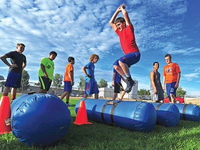 Matt Hinshaw/The Daily Courier<br> Chino Valley High School senior Bud Cain jumps through a drill during summer football practice Tuesday evening at Del Rio Elementary School in Chino Valley. At left, Coach Wade Krug huddles with his squad.