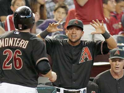 Ross D. Franklin/The AP<br> Arizona Diamondbacks' Miguel Montero celebrates his run scored against the Chicago Cubs with teammate David Peralta, middle, and manager Kirk Gibson, right, during the fifth inning Saturday in Phoenix. Montero had a 3-run double when he batted in the fifth inning.