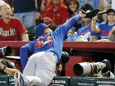 Ross D. Franklin/The Associated Press<br> Chicago Cubs' Anthony Rizzo makes a diving catch into the photo well on a foul ball hit by Arizona Diamondbacks' Aaron Hill during the sixth inning Sunday in Phoenix. Rizzo caught the ball and flipped over the railing. Had Rizzo not gone for the ball and caught it, he would have prevented or delayed the D-backs' go-ahead run.