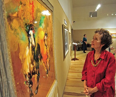 """Matt Hinshaw/The Daily Courier<br> Marie Rhines admires Wei Tai's oil on copper painting, """"Companion,"""" Friday evening during the opening of the Phippen Museum's """"Hold Your Horses"""" exhibit in Prescott."""