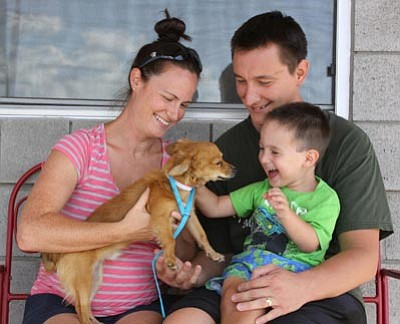 Courtesy photo<br>YHS creates happiness by bringing pets and people together, which is what Stephen, Julie and little Cody Swinkoski experienced when they adopted lovable Cash during the Monsoon Madness.  The event ends Sunday at 5 p.m., so come on down soon to find the love or your life!