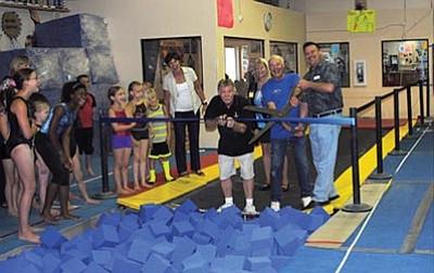 Courtesy photo<br>At the YMCA ribbon cutting, from left, are YMCA gymnasts; Deb Carbone, former YMCA board president; Jon Sebastian, YMCA gymnastics director; Julie Ruttle, YMCA board member; Gary Ballard, Kiwanis Club vice president; and Damon Olsen, YMCA executive director.