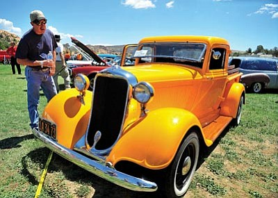 Matt Hinshaw/The Daily Courier<br>Tim Sibson admires a brightly painted 1935 Dodge truck during last year's Prescott Antique Auto Club Watson Lake Car Show, Swap Meet and Old Engine Fire-Up in Prescott.