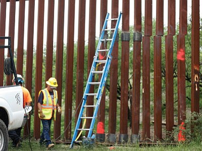 Workers makes repairs to a section of the border fence near Nogales July 27 after suspected smugglers made a garage-sized hole in the steel barrier that divides the U.S. and Mexico. (Curt Prendergast/The Associated Press)