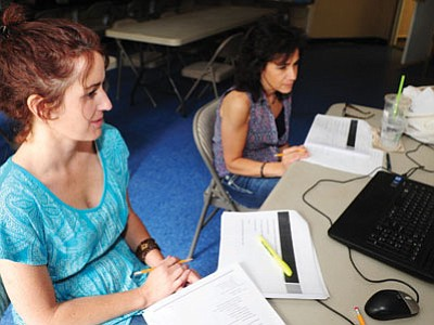 Prescott Prepatory Academy Director Jennifer Womack and secretary Maria Tornambe watch a Skype training session Friday as they prepare for the Aug. 13 opening of the school. (Les Stukenberg/The Daily Courier)