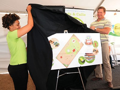 Beneful's Moronke Tyler and DIY Network host Jason Cameron unveil the proposed plan for the $500,000 Willow Creek Dog Park upgrade Wednesday morning. (Les Stukenberg/The Daily Courier)
