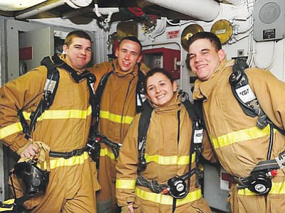 Damage Controlman Second Class Chris Kellogg (left) poses with crewmates on USS Gunston Hall. (Courtesy photo)
