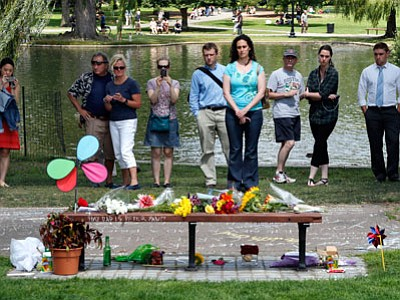 "People pause by a bench at Boston's Public Garden on Tuesday, where a small memorial has sprung up at the place where Robin Williams filmed a scene during the movie, ""Good Will Hunting."" Williams, 63, died at his San Francisco Bay Area home Monday in an apparent suicide. (Elise Amendola/Associated Press)"