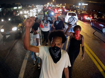 Protesters march down the middle of a street Friday in front of a convenience store that was looted and burned following the shooting death of Michael Brown by police nearly a week ago in Ferguson, Mo. (Charlie Riedel/The Associated Press)