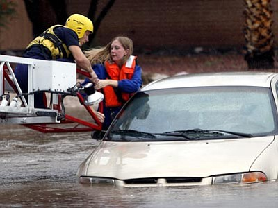 A Tucson Fire Department crew member uses a ladder truck to rescue a woman from a car stranded in rising floodwaters Tuesday. (Kelly Presnell, Arizona Daily Star/The Associated Press)