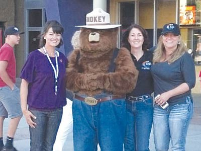Annie Lane, Smokey Bear, Diane Travis and Anessa Andrews pose outside Harkins Theater in Prescott Valley after raising money for the Wildland Firefighters Foundation. (Courtesy photo)