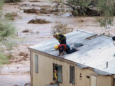 Waters swirl as firefighters rescue a woman from her flooded home in New River on Tuesday. (Mark Henle/The Associated Press)